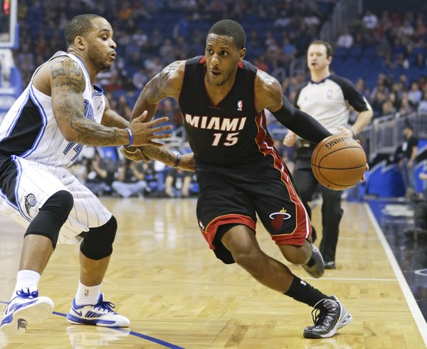 Miami Heat's Mario Chalmers (15) drives around Orlando Magic's Jameer Nelson, left, during the first half of an NBA basketball game in Orlando, Fla., Wednesday, Nov. 20, 2013.(AP Photo/John Raoux)