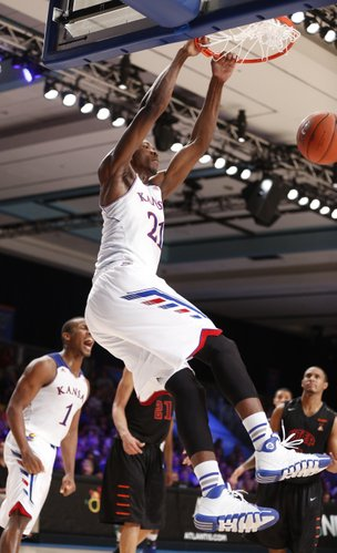 Kansas center Joel Embiid delivers a jam from a lob pass over the UTEP defense during the second half on Saturday, Nov. 30, 2013 in Paradise Island, Bahamas.