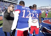 Kansas coach Charlie Weis, left, greets senior Christian Matthews (12) during a senior day celebration before the Jayhawks' game against the Kansas State University Wildcats, Saturday at Memorial Stadium. The Jayhawks lost 31-10 to the Wildcats.