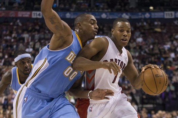Toronto Raptors' Kyle Lowry, right, drives at Denver Nuggets' Darrell Arthur during the second half of an NBA basketball game on Sunday, Dec. 1, 2013, in Toronto. (AP Photo/The Canadian Press, Chris Young)