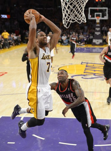 Los Angeles Lakers forward Xavier Henry, left, goes up for a dunk as Portland Trail Blazers guard Mo Williams defends during the second half of an NBA basketball game, Sunday, Dec. 1, 2013, in Los Angeles. (AP Photo/Mark J. Terrill)