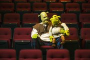 "Knute Pittenger, in costume as Shrek, the title character in Theatre Lawrence's upcoming production, sits in the Theatre Lawrence seats with a stuffed Shrek toy Tuesday. Pittenger has been the lead actor in several Theatre Lawrence musical productions, a far cry from his day job as an employee for the city's Water Department. ""Shrek"" opens Friday at Theatre Lawrence, 4660 Bauer Farm Drive, and runs through Dec. 22."
