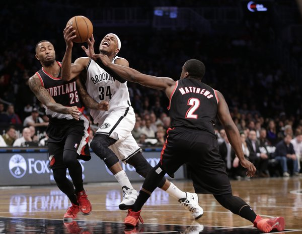 Brooklyn Nets forward Paul Pierce (34) reacts as he is sandwiched between Portland Trail Blazers point guard Mo Williams (25) and Trail Blazers guard Wesley Matthews (2) while driving toward the basket in the first half of their their NBA basketball game at the Barclays Center, Monday, Nov. 18, 2013, in Brooklyn. (AP Photo/Kathy Willens)