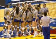 Kansas volleyball players gather around the net during their open practice Thursday at Allen Fieldhouse. The Jayhawks open the NCAA tournament Friday against Wichita State.