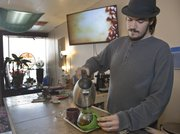 Charles Frager, manager at the artesian tea bar ManaBar, 1111 Massachusetts St., pours hot water to steep tea. Kansas University grads and owners Matthew Rader and Nathan Long opened the business in October.