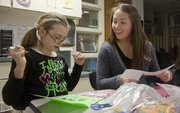 Hannah Moran, right, a volunteer with Big Brothers Big Sisters of Douglas County, creates cards with her Little Sister, Quail Run fourth grader Raigen Hughes.