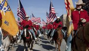 Saddle and Sirloin Club members from Kansas City, Mo., wore red jackets and carried American flags as they helped lead the 21st annual Old-Fashioned Christmas Parade in downtown Lawrence Saturday.