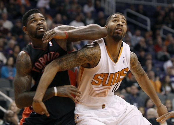 Toronto Raptors' Amir Johnson, left, and Phoenix Suns' Markieff Morris (11) battle for rebound position under the basket during the second half of an NBA basketball game Friday, Dec. 6, 2013, in Phoenix. The Suns defeated the Raptors 106-97. (AP Photo/Ralph Freso)