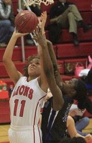 Lawrence High's Makayla Bell (11) shoots over Junction City's Brenna Waterman on Tuesday, Dec. 10, 2013, at LHS.