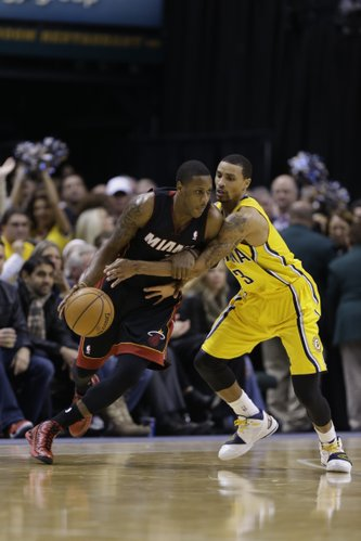 Indiana Pacers guard George Hill, right, defends Miami Heat guard Mario Chalmers in the second half of an NBA basketball game in Indianapolis, Tuesday, Dec. 10, 2013. The Pacers defeated the Heat 90-84. (AP Photo/Michael Conroy)