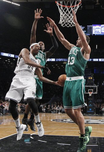 Boston Celtics guard Jeff Green (8) and Celtics forward Kris Humphries (43) defend Brooklyn Nets forward Paul Pierce (34) in the second half of their their NBA basketball game, Tuesday, Dec. 10, 2013, in New York. The Nets defeated the Celtics 104-96. (AP Photo/Kathy Willens)
