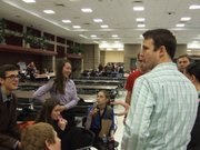 Free State High School debate coach Jason Moore, right, discusses strategy with his teams between rounds at the East Kansas National Forensics League District Tournament this weekend in Olathe. The team of Alex Houston and Hannah Moran, both seniors, made it to the sixth round of the tournament, but missed qualifying to the national tournament.