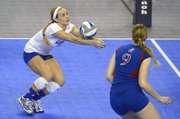 Kansas University libero Brianne Riley, left, digs the ball as Caroline Jarmoc stands by during an NCAA Tournament regional semifinal match against Washington on Friday, Dec. 13, 2013, in Los Angeles