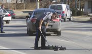 A Lawrence Police officer takes measurements of an accident scene around 1:15 p.m. in the westbound lanes on 6th Street, Monday December 16, 2013. The westbound lanes between Maine and Michigan were closed for about an hour for further investigation.