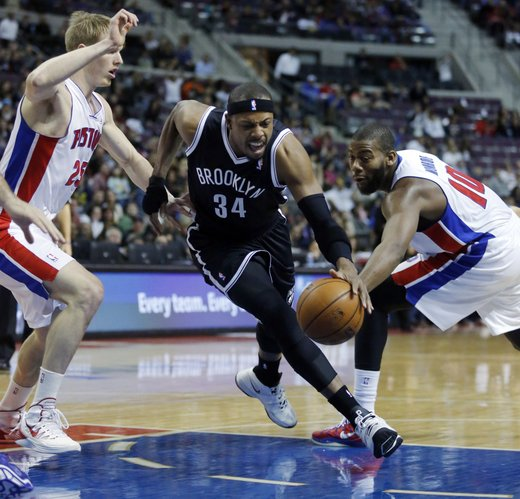 Brooklyn Nets forward Paul Pierce (34) drives to the basket between Detroit Pistons guard Kyle Singler (25) and center Greg Monroe (10) during the first half of an NBA basketball game on Friday, Dec. 13, 2013, in Auburn Hills, Mich. (AP Photo/Duane Burleson)