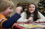 Jennifer Thornton plays a board game with her son Hayden after dinner Dec. 16, 2013. Jennifer is working on her masters in social work from KU and works at the Gillis Center in Kansas City.