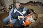 Jason and Jennifer Thornton and their 5-year-old son Hayden share a family moment on the couch at home in Leavenworth. Jason, retired medically from the Army, suffers from PTSD and chronic depression. Jennifer is getting her masters in social work at KU.