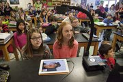 Kaila Bradfield, 11, left, and Hannah Vaughn, 12, watch a big screen with a live feed from Antarctica on Tuesday morning as their class talked with Carl Leuschen about his research there.