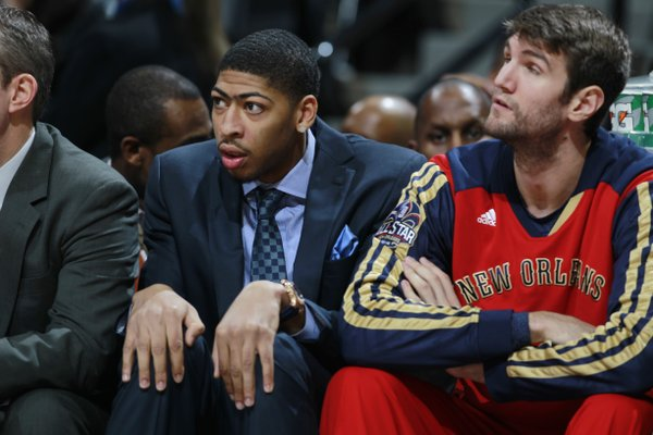 New Orleans Pelicans forward Anthony Davis, left, who is injured, sits on bench with rookie center Jeff Withey as the Pelicans face the Denver Nuggets in the first quarter of an NBA basketball game in Denver on Sunday, Dec. 15, 2013. (AP Photo/David Zalubowski)