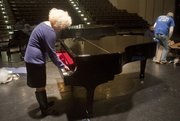 Margaret Morris, executive director of programs and partnerships at the Lawrence Arts Center, plays a few notes on the Arts Center's new Steinway piano just after it was unwrapped Thursday.