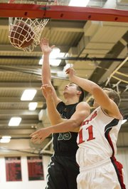 Free State senior Keith Loneker (15) slips past Lawrence High sophomore Price Morgan (11) for an easy two during their game Friday at LHS.