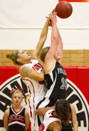 Lawrence High senior Kionna Coleman, left, defends an entry pass to Free State freshman Madison Piper during their game Friday at LHS.