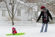 Linda Redding pulls her son Oliver Hester, 3, in his sled Sunday morning on the New York school playground. The Lawrence area received about 6-inches of snow Saturday night and into Sunday morning.