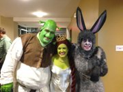 "Jake Leet, right, in his Donkey costume with cast mates before a performance of ""Shrek"" at Theatre Lawrence."