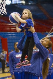 Kansas freshman Caelynn Manning-Allen lifts Avery True, 5, of Topeka, for a basket during the KU women's basketball holiday clinic, Friday, Dec. 27, 2013, at Allen Fieldhouse.