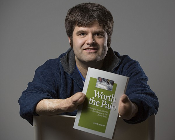 "Andy Marso poses with his book, ""Worth the Pain,"" which details his battle with meningitis and how it changed his life."