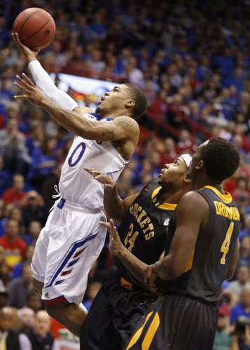 Kansas guard Frank Mason puts up a layup against Toledo defender J.D. Weatherspoon (24) and Justin Drummond (4) during the first half on Monday, Dec. 30, 2013 at Allen Fieldhouse.
