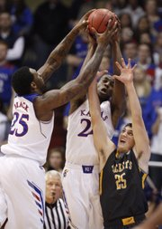 Kansas defenders Tarik Black and Andrew Wiggins get up for a loose ball over Toledo guard Jordan Lauf during the first half on Monday, Dec. 30, 2013 at Allen Fieldhouse.