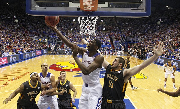 Kansas center Joel Embiid dips under the bucket for a reverse layup after being fouled by Toledo center Nathan Boothe during the second half on Monday, Dec. 30, 2013 at Allen Fieldhouse.