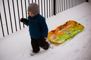 The Kid pulls his new toboggan before going sledding for the first time.