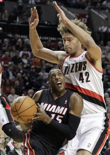 Miami Heat guard Mario Chalmers, left, drives against Portland Trail Blazers center Robin Lopez during the first half of an NBA basketball game in Portland, Ore., Saturday, Dec. 28, 2013. (AP Photo/Don Ryan)