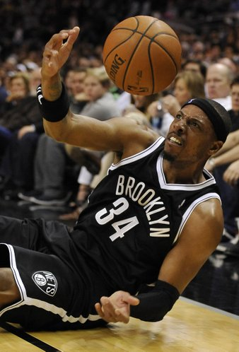 Brooklyn Nets forward Paul Pierce slides out of bounds as he chases the loose ball during the first half of an NBA basketball game against the San Antonio Spurs on Tuesday, Dec. 31, 2013, in San Antonio. (AP Photo/Darren Abate)