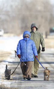 Lawrence residents Jan and Chris Holmer are all bundled up as they take a morning walk with their dogs, Robbie and Nellie, on Friday, Jan. 3, 2014 in North Lawrence. Nick Krug/Journal-World Photo