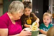 Child care provider June Roush cooks with Taiven Hanson, center, and Barrett Maimer, right, during a 2013 Healthy Sprouts farm-to-preschool activity in Baldwin City.