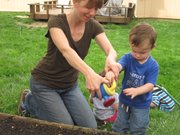 Emily Hampton, farm-to-preschool coordinator for Healthy Sprouts, waters a garden with Cade Privat at a Lawrence in-home child care provider in this 2013 photo.