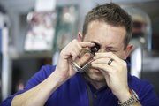 Jeff Neal, operating partner at Sunflower Pawn and Jewelry, 2429 Iowa St., uses a loupe to examine a Rolex watch being sold by a customer on Friday.
