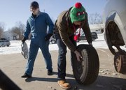 In temperatures around 3 degrees, Kenden Christenson, left, and David Hammons change a flat tire on Christenson's car Monday in the parking lot of Sun Creations Inc., 826 Pennsylvania, where the two work.