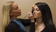 Liz Black applies eye shadow to Beth Grimm, 27 of Bonner Springs. Pantone's 2014 color of the year is Radiant Orchid.