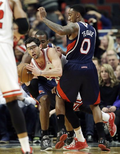 Chicago Bulls guard Kirk Hinrich, center, looks to pass as Atlanta Hawks forward Paul Millsap, left, and guard Jeff Teague guard during the first half of an NBA basketball game in Chicago on Saturday, Jan. 4, 2014. (AP Photo/Nam Y. Huh)