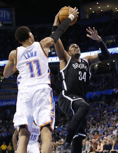 Brooklyn Nets forward Paul Pierce (34) shoots in front of Oklahoma City Thunder guard Jeremy Lamb (11) during an NBA basketball game between the Brooklyn Nets and the Oklahoma City Thunder in Oklahoma City, Thursday, Jan. 2, 2014. (AP Photo/Sue Ogrocki)