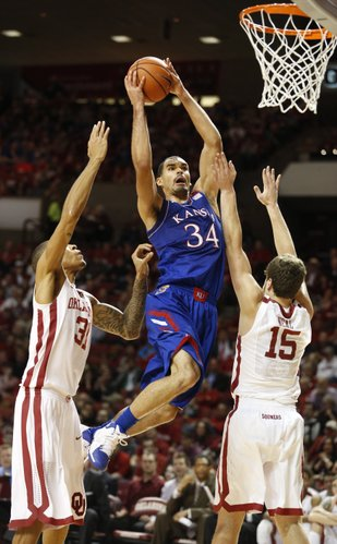Kansas forward Perry Ellis elevates to the bucket between Oklahoma defenders D.J. Bennett (31) and Tyler Neal (15) during the first half on Wednesday, Jan. 8, 2013 at Lloyd Noble Center in Norman, Oklahoma.