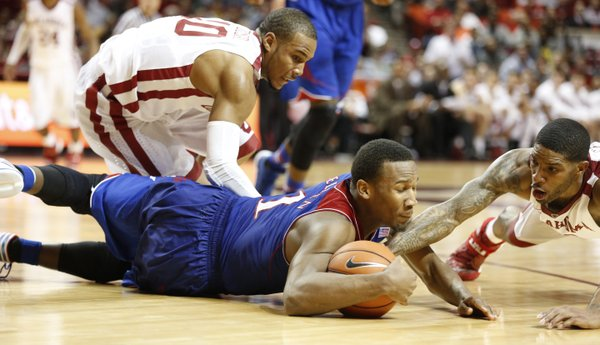 Kansas guard Wayne Selden gets on the floor to secure a loose ball from Oklahoma defenders Jordan Woodard (10) and Cameron Clark late in the second half on Wednesday, Jan. 8, 2013 at Lloyd Noble Center in Norman, Oklahoma.