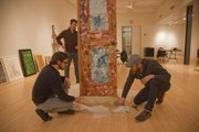 From left, Yuri Zupancic, Ben Ahlvers and Jeremy Rockwell unwrap artwork by William Burroughs on Friday at the Lawrence Arts Center.