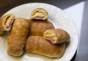 Hand sandwiches with horseradish mustard, roast beef, sour cream and cheddar cheese wrapped in pizza dough