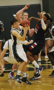 Free State junior Justin Narcomey (25) collects a rebound against Olathe North's Josh Moore (32) on Friday, Jan. 10, 2014, at FSHS.