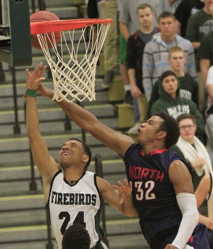 Firebirds senior Reshawn Caro (24) gets fouled by Olathe North's Josh Moore (32) on Friday, Jan. 10, 2014, at FSHS.
